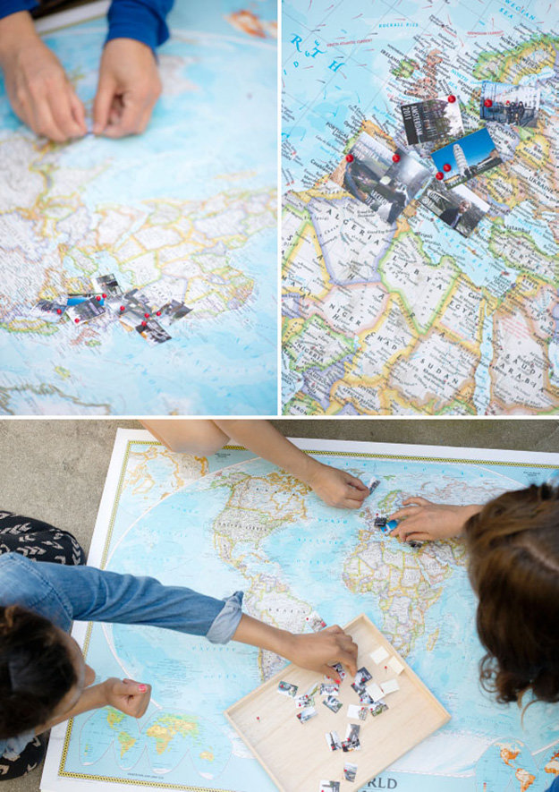 three people pinning small images, on a large world map, close ups reveal, that the images are tiny photos of landmarks