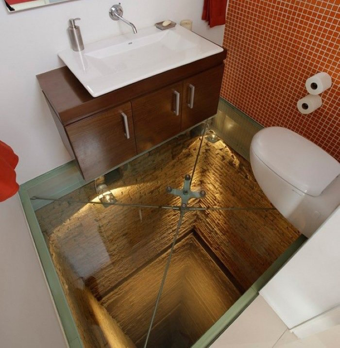 bathroom remodels, small toilet with two white walls, one wall covered by orange mosaic, brown wooden cupboard with flat white sink, white toilet seat, see through glass floor, revealing deep tunel beneath