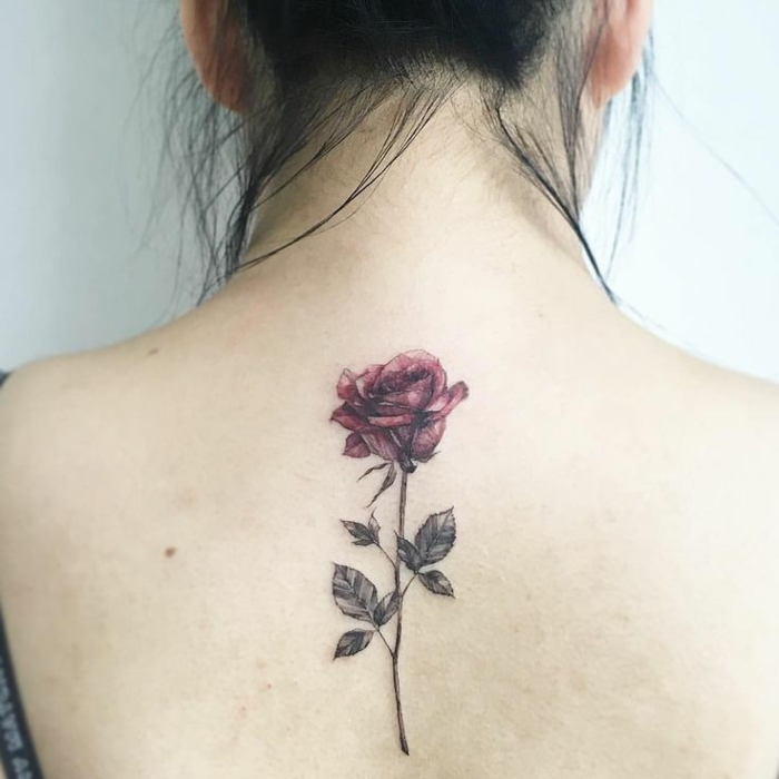 flower tattoos, close up of a woman's bare back, black hair put up, with a realistic rose tattoo, in dark pink and grey-green