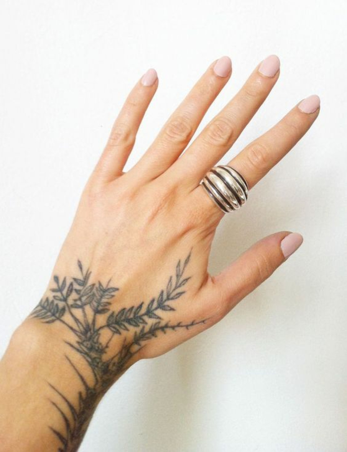 traditional flower tattoo, close up of a female hand, with pale pink nail polish, and large silver and black striped ring, a tattoo of a leafy plant going up the arm, and down towards the index finger