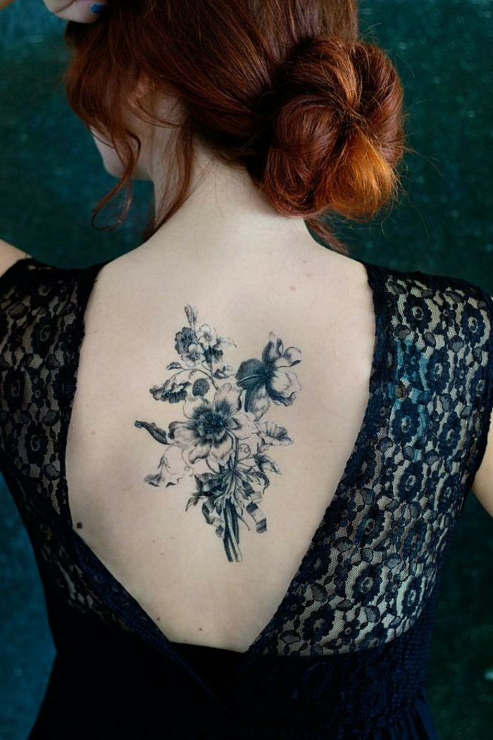 traditional flower tattoo, red-haired woman with hair pulled in a bun, wearing an open back, dark blue lace dress, revealing a large tattoo of a flower bouquet, made up of many different plants, in blue ink