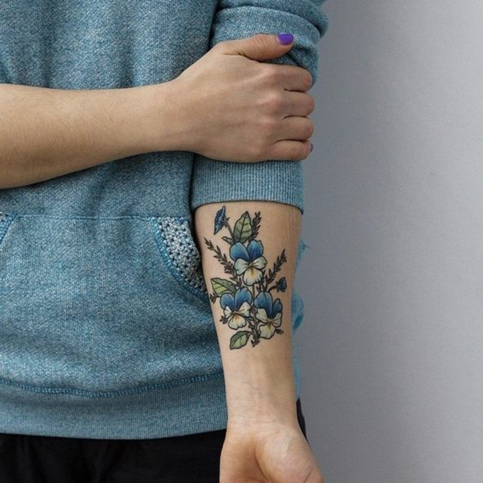 botanical tattoo, woman in pale blue sweater,with rolled up sleeves, holding her arm, with a tattoo of three pansies, in blue and yellow, with several buds and green leaves