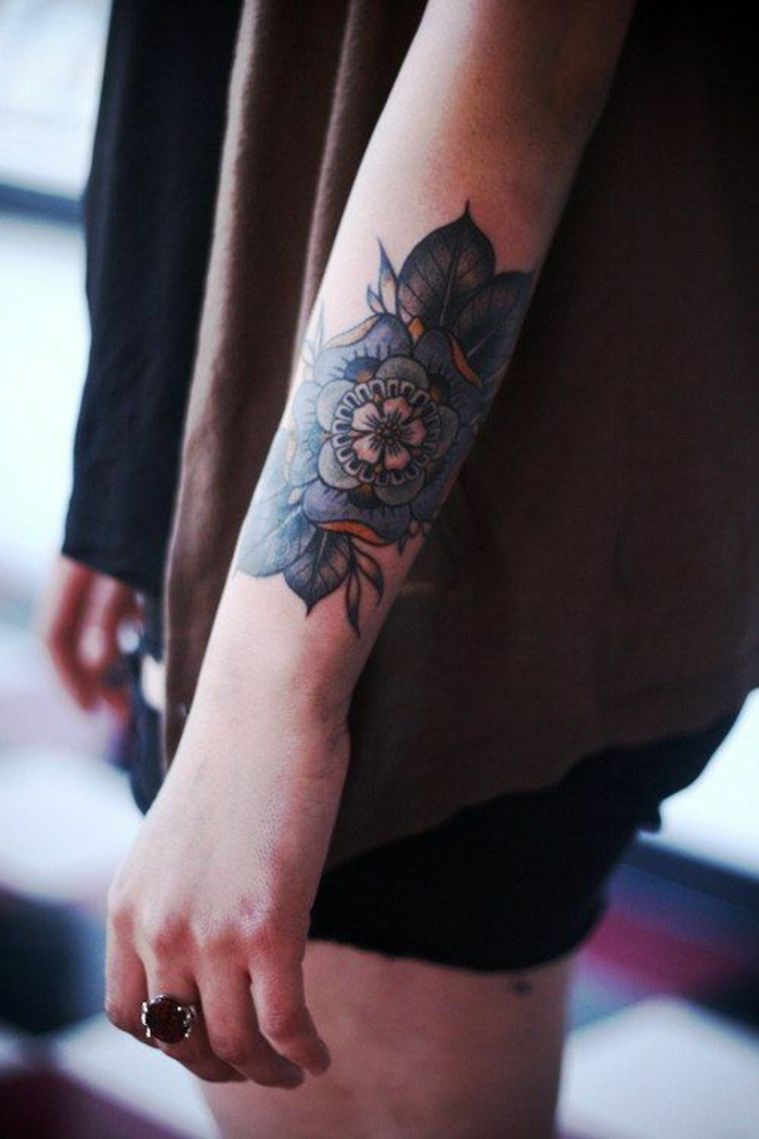 traditional flower tattoo, close up of a female lower arm, with an elaborate blue, green and yellow tattoo, with several rows of petals and green leaves, reminiscent of the tudor rose