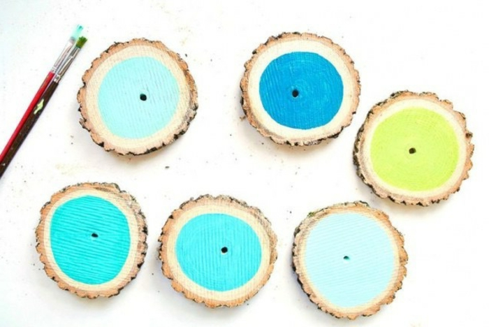 six round slices of wood, with bark, painted in different shades of blue and green, diy craft projects, paint brush nearby