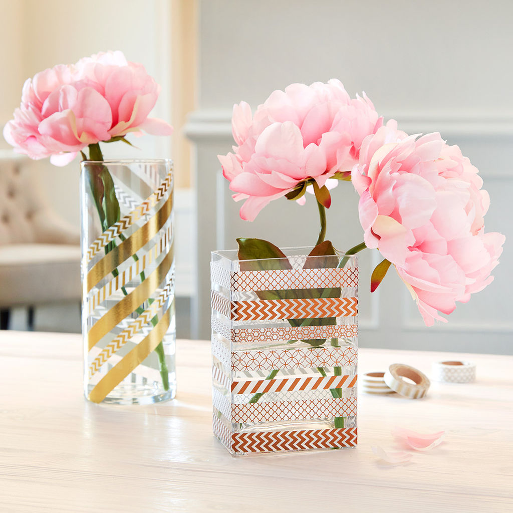 two clear vases, one round one rectangular, containing pink peonies, decorated with patterned washi tape, in gold and light brown, art and craft ideas