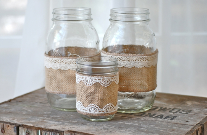 decorating mason jars, two large and one small jar, with beige burlap and white lace, placed on an overturned wooden crate