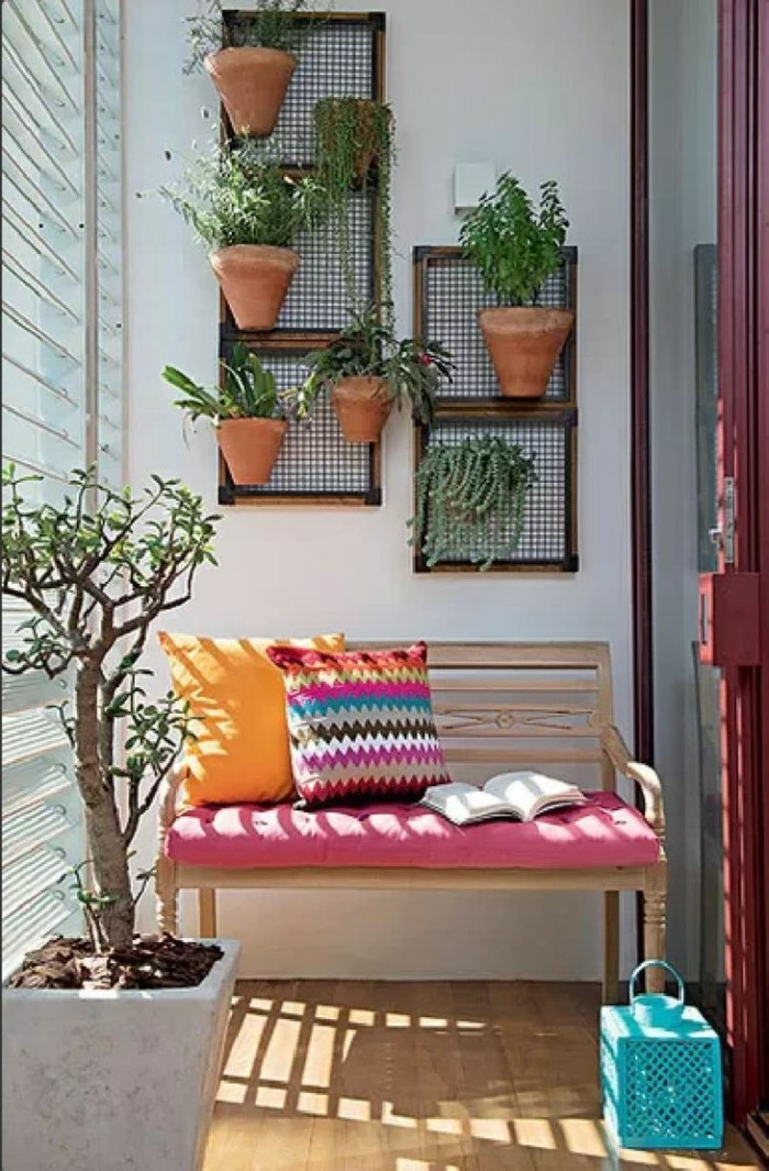 front porch décor, wooden bench with pink cover, two multicolored cushions, and a book, front porch décor, many potted plants on wall