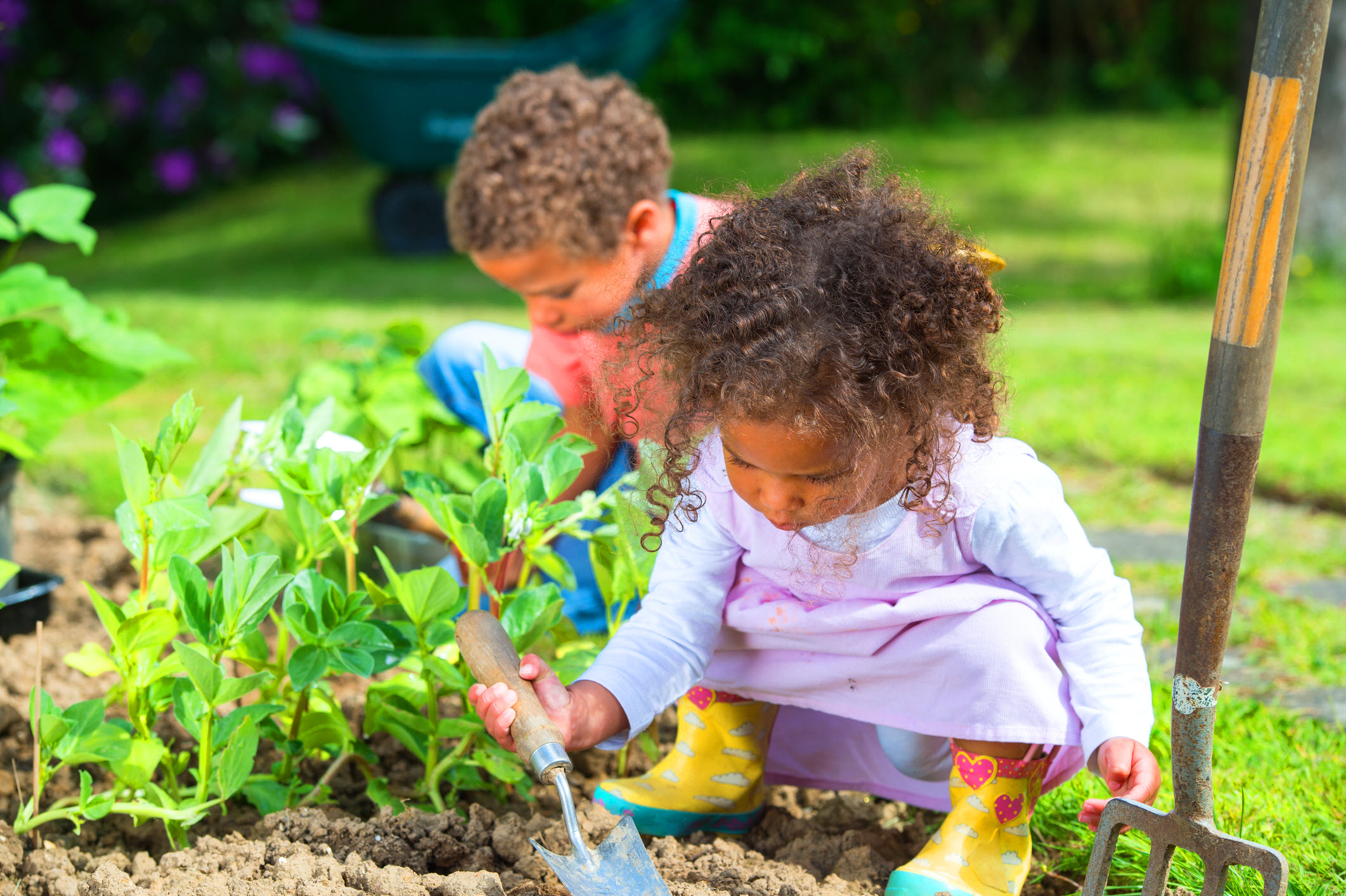two small children, a boy and a girl, gardening near green plants