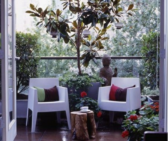 two white chairs with pillows, tree stump table with tea cup, lots of plants and greenery, near buddha statue, outdoor patio ideas