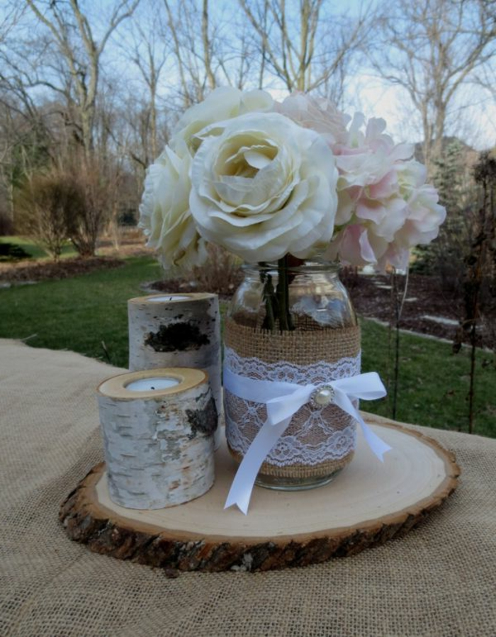 mason jar crafts, clear jar decorated with burlap, white lace and a ribbon with bow, containing white and pale pink flowers, candles nearby