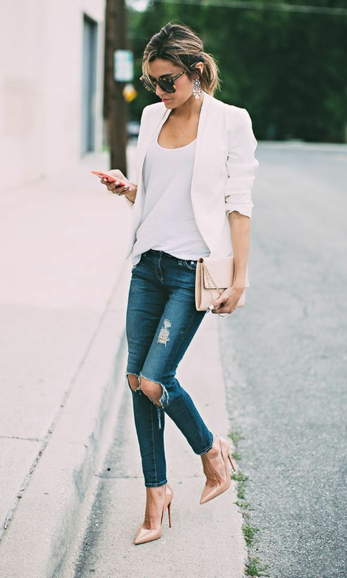 torn and distressed business casual jeans, combined with white top, and white blazer, worn by woman in nude high heels, holding matching clutch