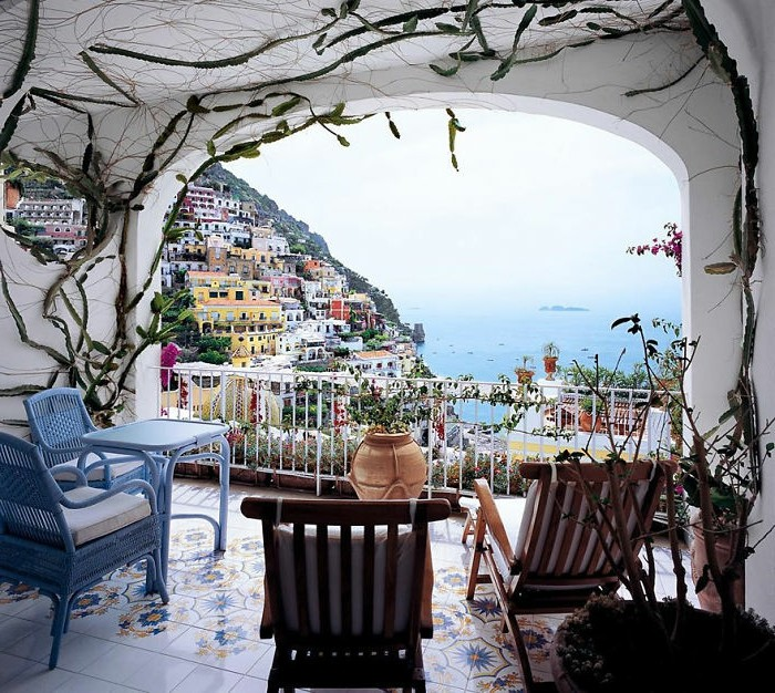 pale blue chairs and table set, wooden lounging chairs, white walls and ceiling with ivy-like cacti, porch décor and beautiful view