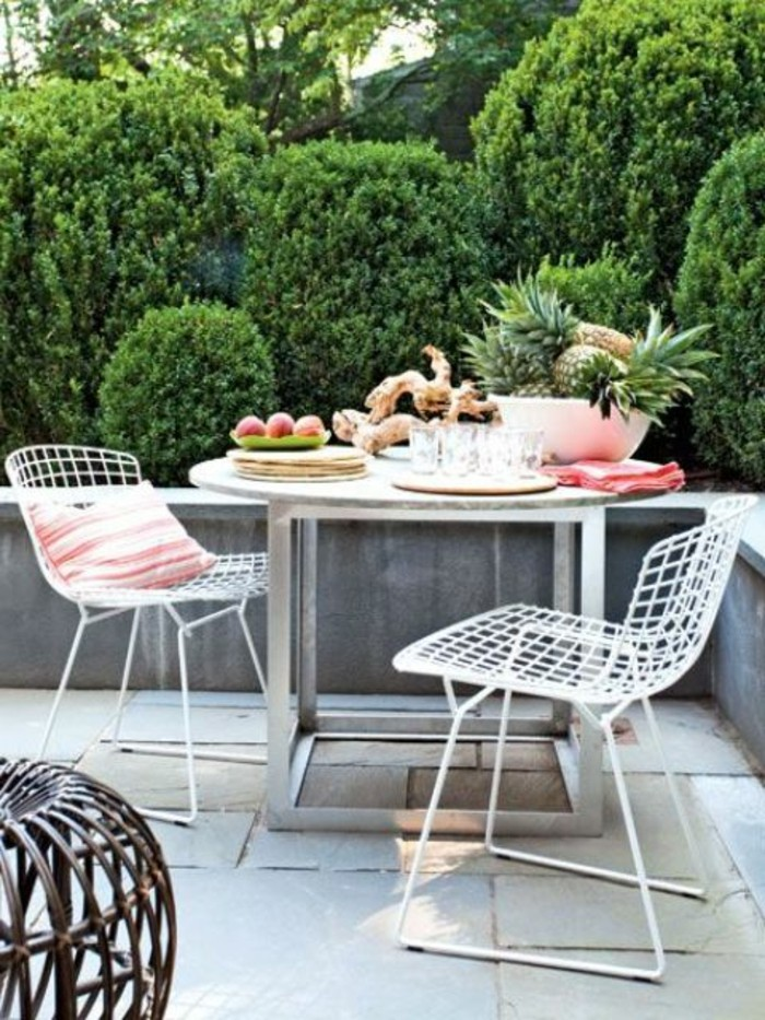 round metal table, with fruit and decorations, and two white chairs, one with pink striped pillow, outdoor patio ideas, greenery in background