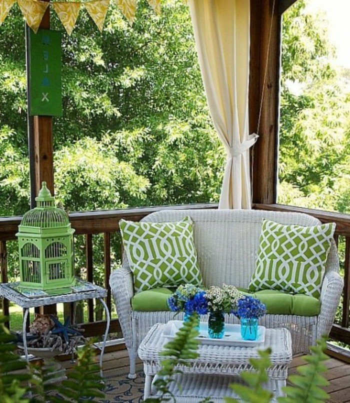 pale grey wicker settee with two matching tables, one with decorative green metal birdcage, the other with tree vases with flowers on a tray, covered patio ideas, wooden beams and curtains, greenery and potted plants
