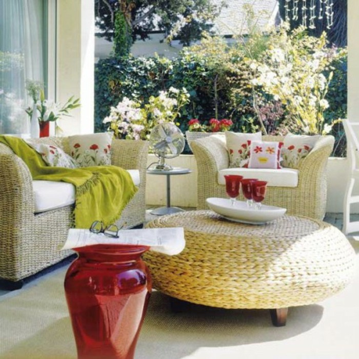 wicker furniture in a set, featuring couch and cozy chair, and a round table, front porch décor, with pillows and blanket, big red vase and decorations
