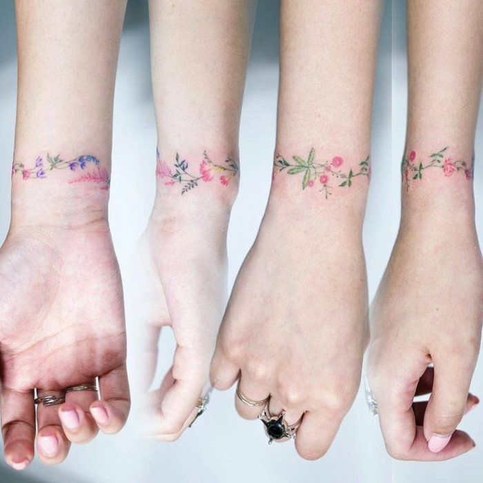 wildflower tattoo, a wrist bracelet-type tattoo, seen from all angles, with many tiny, intertwining flowers and leaves, in pink and purple, blue green and red