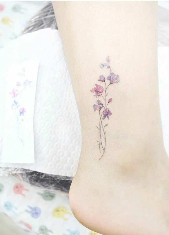 wildflower tattoo, three pale pink and purple flowers, with thin green stalks, tattooed on a person's ankle