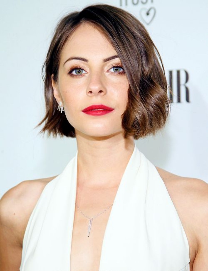 smiling willa holland, wearing white halter neck top, and red lipstick, side parted wavy hair, short bob hairstyles