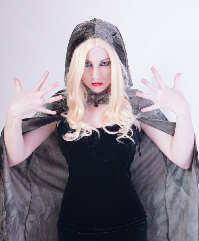 woman in blonde wig with curly ends, wearing black tight dress, and grey velvet hooded cape, heavy make up, and theatrical pose
