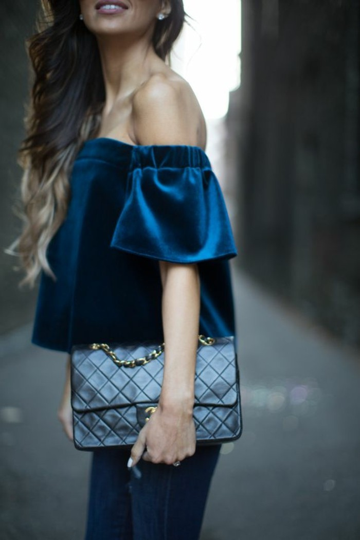 business casual women, dark blue velvet off-shoulder top, worn over dark jeans, by woman with wavy ombre blonde hair, holding black leather bag