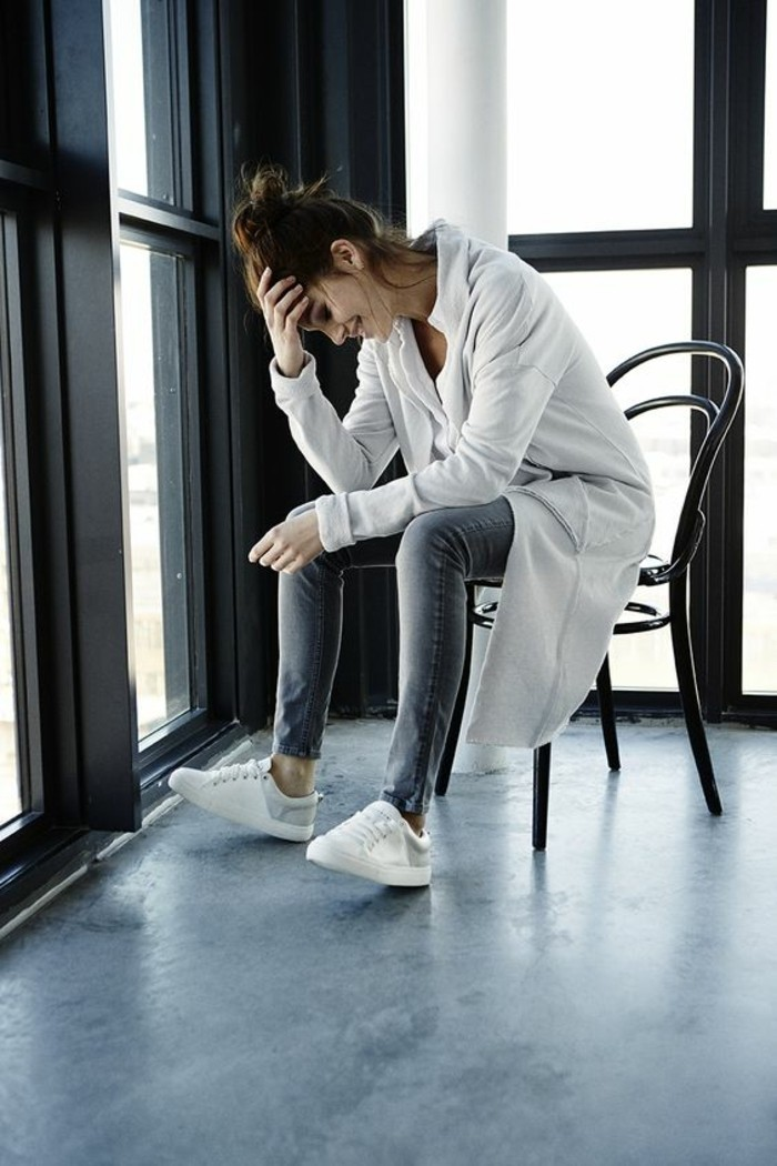casual business attire, smiling brunette with messy top knot, sitting on a chair and holding her head with one hand, wearing grey skinny jeans, white sneakers and top, and long white cardigan