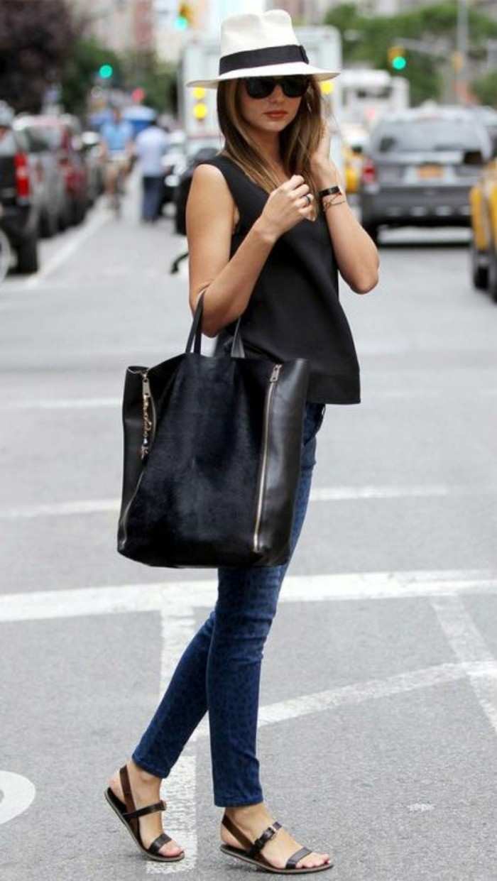 business casual women, black sleeveless top, dark blue jeans, and brown flat sandals, worn by woman in white fedora and sunglasses