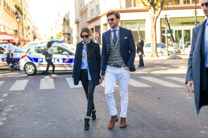 business casual for young women, brunette woman with pale blue shirt, dark jeans and navy blue coat, walking next to man in white trousers, with grey vest, pale shirt and dark tie