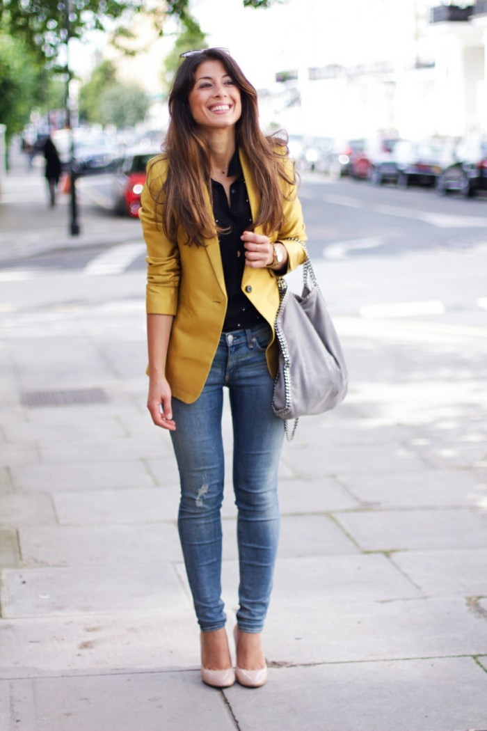 casual business attire, yellow blazer and black shirt, worn with distressed jeans, pale cream pumps and grey slouchy bag, by smiling brunette with long hair