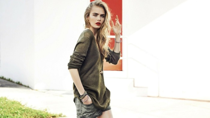casual clothes, cara delevingne with red lipstick blond wavy hair, wearing khaki green sweater, and grey denim shorts