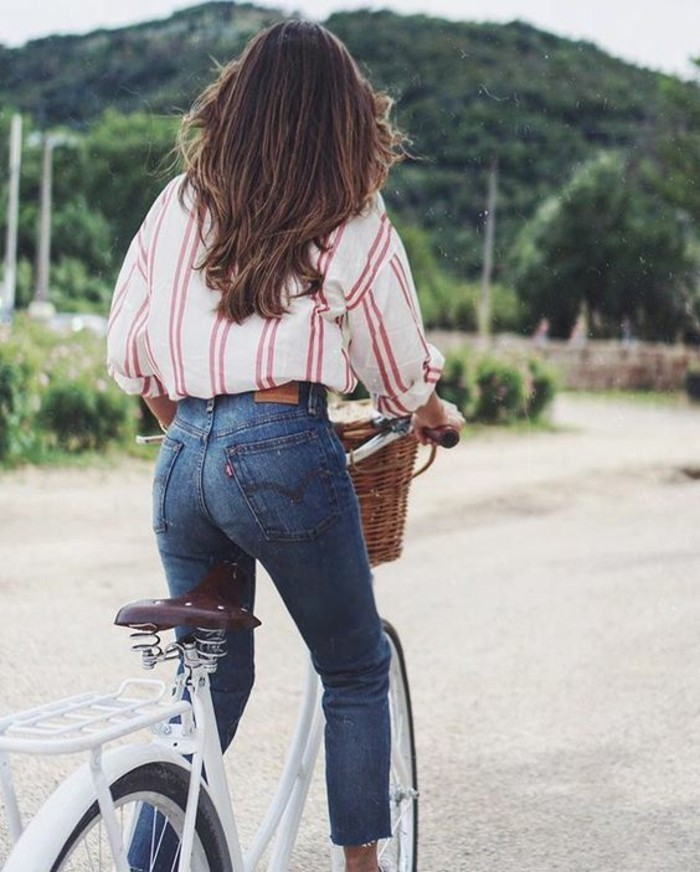 women outfits, oversized white shirt with red stripes, tucked into skinny jeans, worn by brunette woman on bike