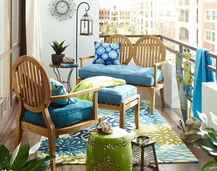 double wooden settee, with blue cover and patterned cushion, matching chair and table, porch décor, green and blue ornate rug, various decorative objects