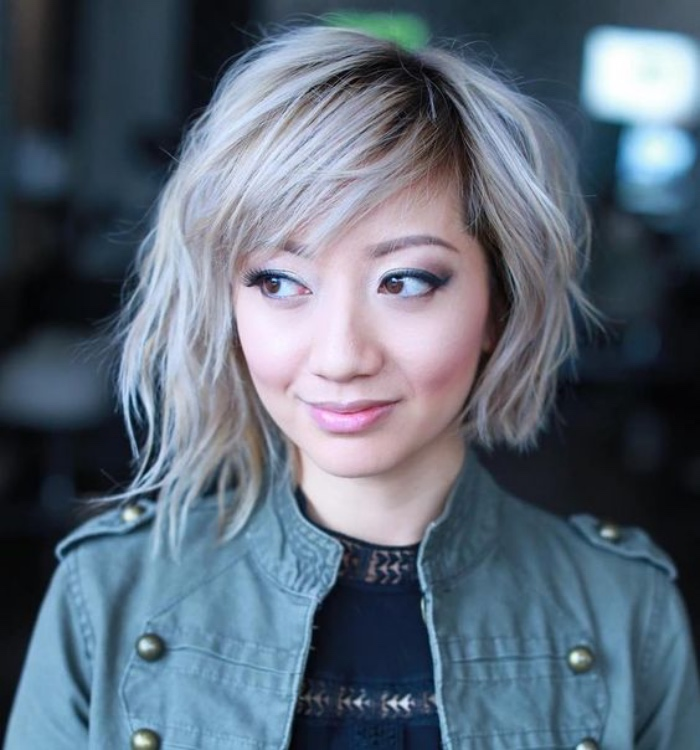 asymmetrical wavy hair, dyed platinum blonde, longer on one side, with side bangs and dark roots, worn by smiling woman, in pale green jacket, short bob hairstyles