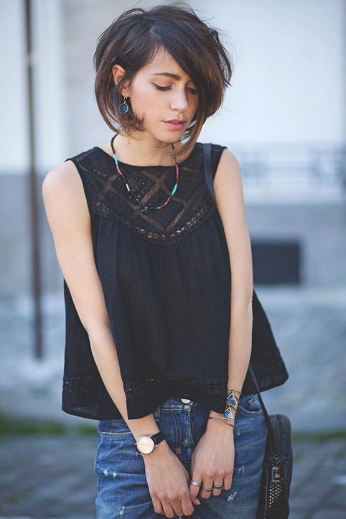 black sleeveless top, dark denim jeans, worn by young woman, with dark brunette, side-parted voluminous bob haircut