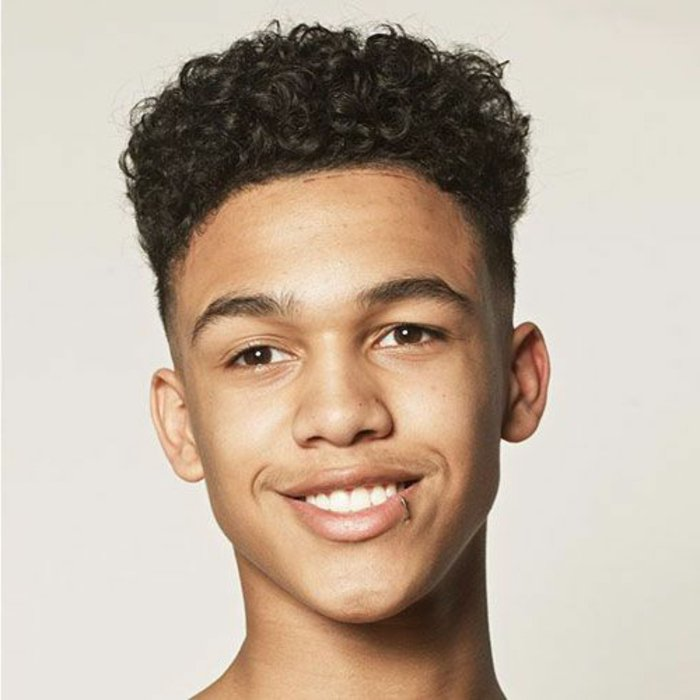 boys fade haircut, dark brown curly afro hair, on a smiling young boy, with lip piercing, disconnected undercut