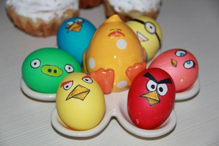 ceramic egg holder with chick figurine, with six easter eggs, made to look like five angry birds' characters, and a minion