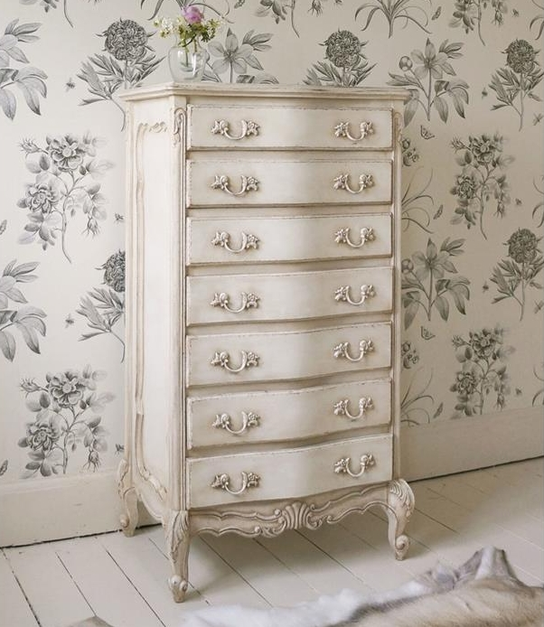 chest of drawers in antique style, painted in shabby cream color, country cottage furniture, on white floor, near goatskin rug, and floral wallpaper in white and grey