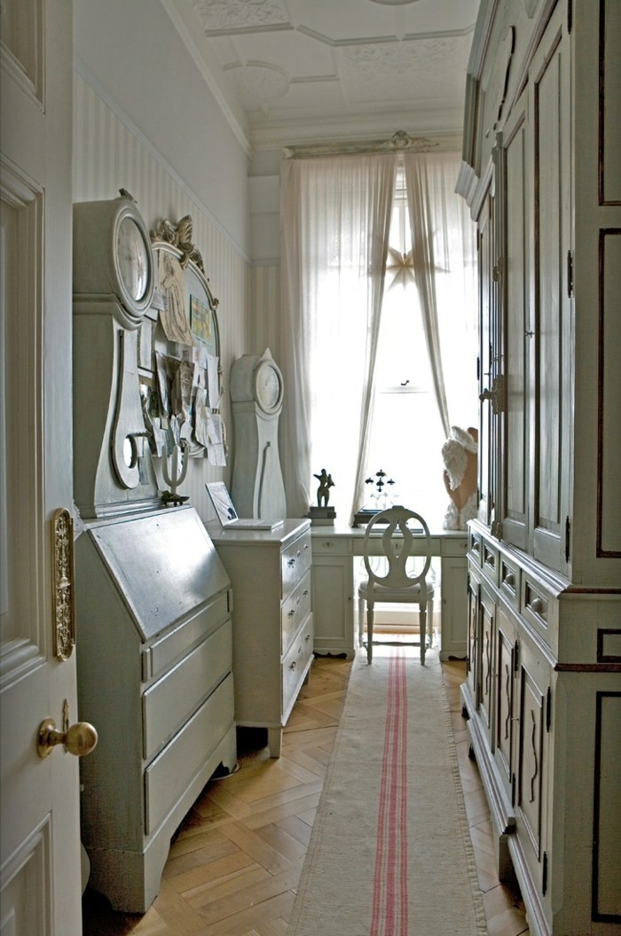 long hallway runners, pale wooden laminate floor, white antique furniture, including a wardrobe, several cupboards and a desk, with a matching chair, long beige rug, with three pink stripes