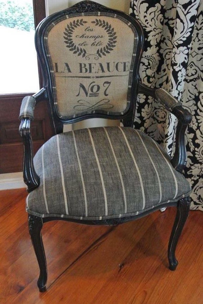 dark grey chair with cream stripes, graphic print on its backrest, black legs and armrests, vintage french style