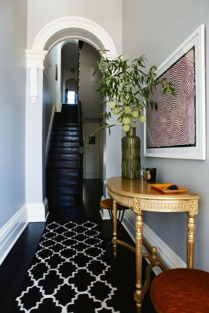 archway leading to a black staircase, black shiny floors, wooden table and two stools, framed abstract artwork, black and white patterned rug, long hallway runners