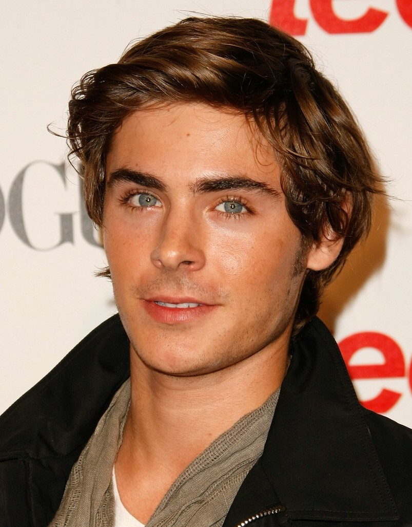 wavy tousled brunette hair, with deep side part, worn by zac efron, hair designs for boys, with scarf and winter jacket