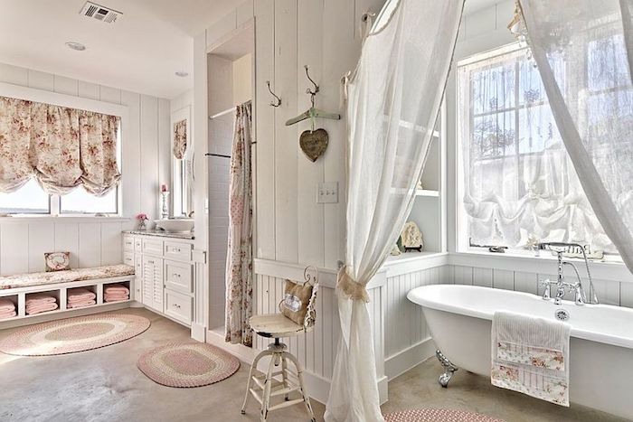 floral curtains in cream and pink, inside a bathroom with white wooden paneling, and smooth beige floor, white bathtub with silver ornamental legs, shabby chic decorating, sheer white curtains