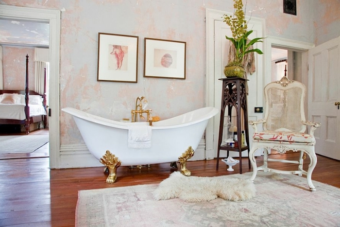 bathtub in white, with golden ornamental legs, shabby chic furniture, on wooden floor with faded rug, and fluffy lambskin throw, near antique chair and various decorations
