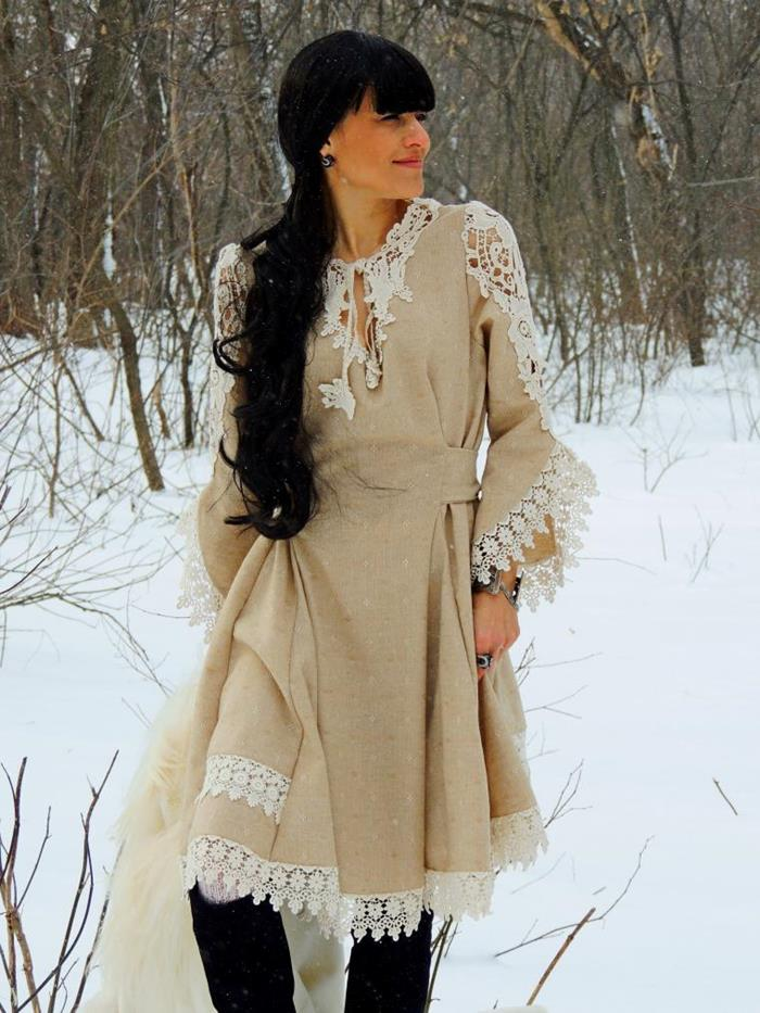 beige boho chic dress, with white lace trim, on woman with knee-high black boots, and long black hair with bangs