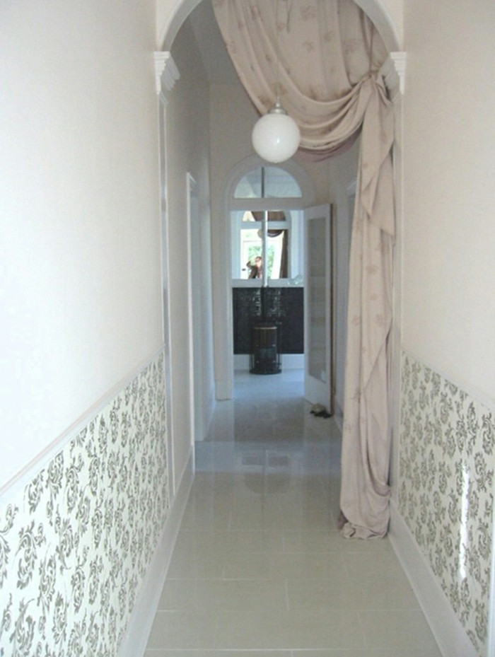archway entry with pale beige curtain, leading into a narrow corridor, with white walls, partially covered with black and white floral wallpaper, small hallway ideas