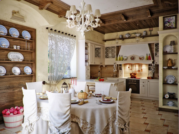 spacious kitchen with tiled floor, old-fashioned black stove, round table covered with beige fabric, and six matching chairs, shabby sheek interior