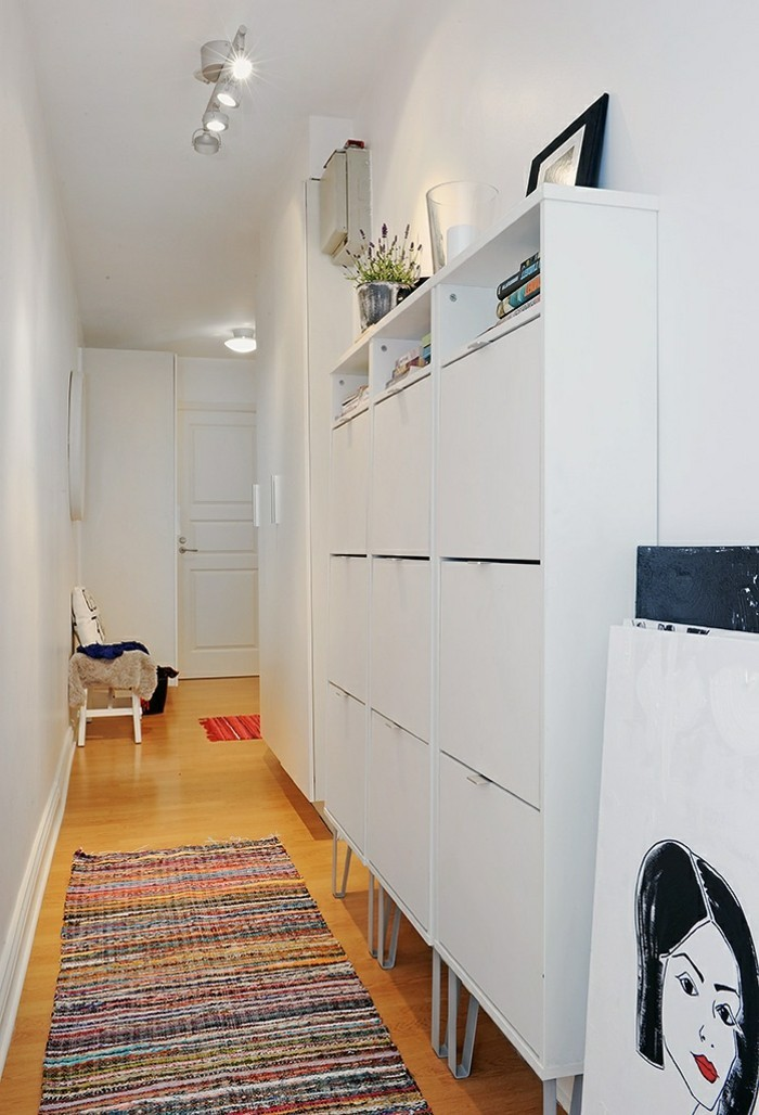 modern hallway with white walls, pale orange laminate floor, white cupboard and multicolored rug