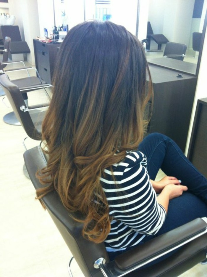 woman sitting on hairdresser's chair, with dark blue jeans, and white and black striped top, partially curled long, brown highlighted hair, with dark roots, and honey-blonde ends