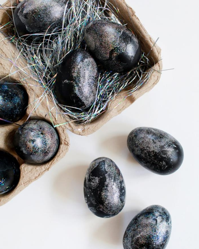 sparkly black eggs, covered in iridescent glitter, part of them are placed in a cardboard egg box, filled with hologram colored easter grass, others are placed on the table