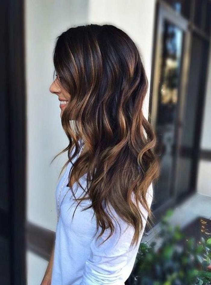blonde balayage on curled brunette hair, dark brown hair colors, on smiling woman, in pale sweater, facing to the side