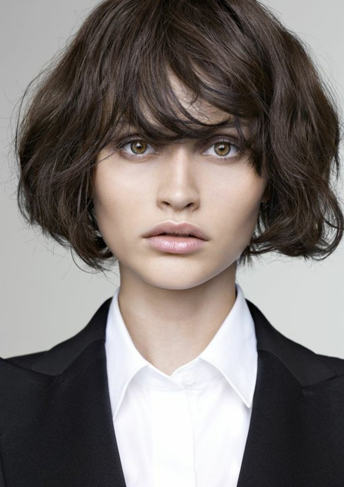wavy bobbed hair, with messy side bangs, brunette hairstyles, worn by woman with hazel eyes, wearing white shirt and black blazer